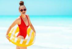 Glimlachende vrouw op zeekust die gele opblaasbare reddingsboei dragen royalty-vrije stock fotografie