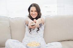 Glimlachende vrouw in pyjama die popcorn hebben terwijl het letten van op TV royalty-vrije stock afbeelding