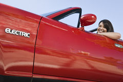 Glimlachende Vrouw in Rode Elektrische Auto royalty-vrije stock afbeelding