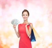 Glimlachende vrouw in rode kleding met het winkelen zakken Stock Fotografie