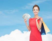 Glimlachende vrouw in rode kleding met het winkelen zakken Stock Afbeelding