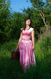 Glimlachende vrouw in roze kleding met koffer Stock Foto's