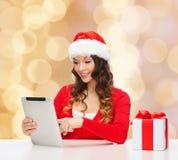 Glimlachende vrouw in santahoed met gift en tabletpc Stock Afbeeldingen