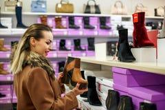 Glimlachende vrouw in schoenenopslag het winkelen Royalty-vrije Stock Afbeelding