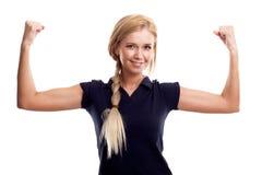 Glimlachende vrouw in sportenslijtage die haar bicepsen toont stock fotografie