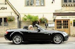 Glimlachende vrouw in sportwagen stock foto