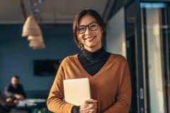 Glimlachende vrouw in toevallig in bureau stock fotografie