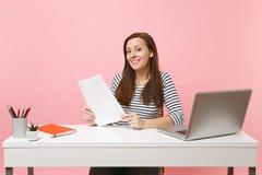 Glimlachende vrouw in vrijetijdskleding die document documenten houden en aan project werken terwijl het zitten op kantoor met la stock foto