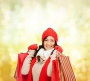 Glimlachende vrouw in warme clothers met het winkelen zakken royalty-vrije stock afbeelding