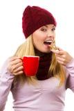 Glimlachende vrouw in wollen GLB en sjaal met peperkoekkoekjes en thee, witte achtergrond, Kerstmistijd royalty-vrije stock foto
