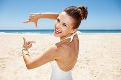 Glimlachende vrouw in zwempak bij het zandige strand ontwerpen met handen Royalty-vrije Stock Foto