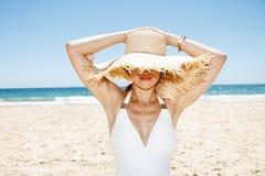 Glimlachende vrouw in zwempak het verbergen onder grote strohoed bij strand Stock Afbeelding