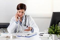 Glimlachende Vrouwelijke apotheker op de geneeskunde van de telefoonholding royalty-vrije stock afbeelding
