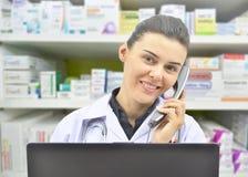 Glimlachende vrouwelijke Apotheker Talking aan iemand op Telefoon op apotheekachtergrond stock afbeelding
