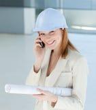 Glimlachende vrouwelijke architect met bouwvakker op telefoon Stock Afbeeldingen