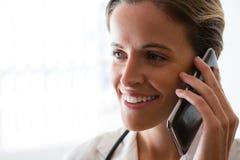Glimlachende vrouwelijke arts die op mobiele telefoon in verpleeghuis spreken Stock Foto