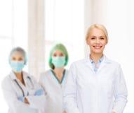 Glimlachende vrouwelijke arts met groep dokters Stock Foto