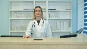 Glimlachende vrouwelijke arts met stethoscoop bij de ontvangst Stock Afbeeldingen