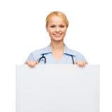 Glimlachende vrouwelijke arts of verpleegster met lege raad Royalty-vrije Stock Afbeeldingen