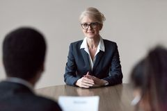 Glimlachende vrouwelijke baankandidaat die op middelbare leeftijd eerste indruk maken bij gesprek stock afbeelding