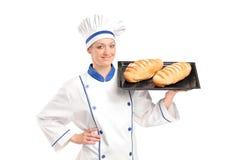 Glimlachende vrouwelijke bakker die vers gebakken broden toont Royalty-vrije Stock Foto