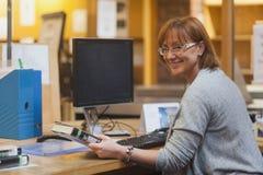Glimlachende vrouwelijke bibliothecaris een boek houden die zich bevindt achter het bureau stock foto's