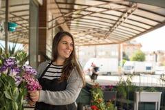 Glimlachende vrouwelijke bloemist in een bloemwinkel royalty-vrije stock fotografie