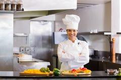 Glimlachende vrouwelijke chef-kok met gesneden groenten in keuken Stock Foto's