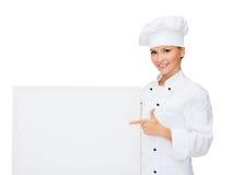 Glimlachende vrouwelijke chef-kok met witte lege raad Royalty-vrije Stock Foto