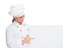 Glimlachende vrouwelijke chef-kok met witte lege raad Stock Afbeeldingen