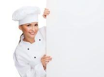 Glimlachende vrouwelijke chef-kok met witte lege raad Royalty-vrije Stock Fotografie