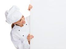 Glimlachende vrouwelijke chef-kok met witte lege raad Stock Foto