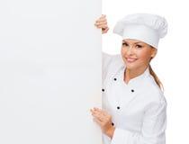 Glimlachende vrouwelijke chef-kok met witte lege raad Stock Foto's
