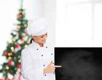 Glimlachende vrouwelijke chef-kok met witte lege raad Stock Fotografie