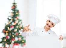 Glimlachende vrouwelijke chef-kok met witte lege raad Stock Afbeelding