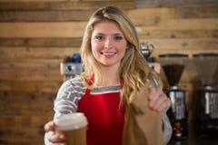 Glimlachende vrouwelijke de koffiekop van de baristaholding en document zak in cafetaria stock foto's