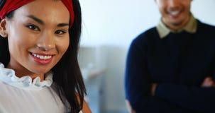 Glimlachende vrouwelijke en mannelijke stafmedewerkers die zich in bureau 4k bevinden stock videobeelden