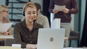 Glimlachende vrouwelijke helpline exploitant met hoofdtelefoons bij haar bureau in het bureau stock videobeelden
