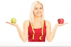 Glimlachende vrouwelijke holding twee appelen en het meten van band rond haar Stock Afbeeldingen