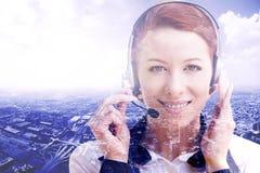 Glimlachende vrouwelijke klantenondersteuningsexploitant met hoofdtelefoon op cityscape achtergrond Royalty-vrije Stock Foto's