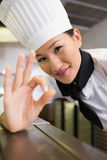 Glimlachende vrouwelijke kok die o.k. teken in keuken gesturing Royalty-vrije Stock Foto's