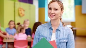 Glimlachende vrouwelijke leraar in de kleuterschool stock footage