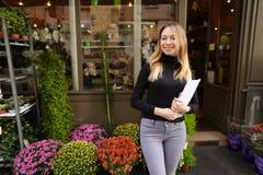 Glimlachende vrouwelijke manager die van bloemwinkel zich met documenten bevinden stock foto's