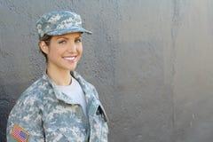 Glimlachende vrouwelijke militair die zich met exemplaarruimte bevinden royalty-vrije stock afbeelding