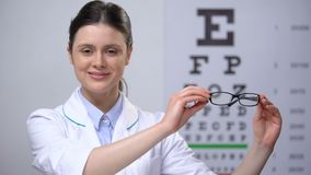 Glimlachende vrouwelijke oftalmoloog die oogglazen, zichtcorrectie adviseren stock video