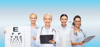 Glimlachende vrouwelijke oogartsen en verpleegsters Stock Foto's