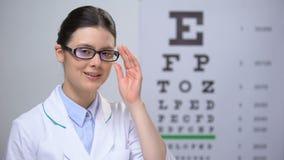 Glimlachende vrouwelijke optometrist het aanpassen glazen en het kijken aan professionele camera, stock video
