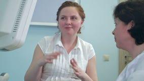 Glimlachende vrouwelijke patiënt die aan een arts voor ultrasone klankapparaat spreken stock footage