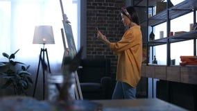 Glimlachende vrouwelijke schilder die nieuw kunstwerk fotograferen stock footage
