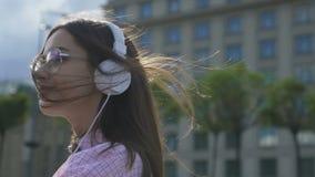 Glimlachende vrouwelijke student die in oortelefoons van stedelijk weekend genieten in openlucht, vrijheid stock video